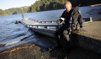 ADVANCE FOR THE WEEKEND OF OCT. 22-23 AND THEREAFTER - In a Sept. 28, 2016 photo, Bandon Dive Team dive chief Bob Hood removes his gloves after exiting the water at Eel Lake during a training session in William M. Tugman State Park near Lakeside, Ore. In 1994, he and a few other divers formed an unofficial team because they had all done commercial diving in the past and wanted to put their skills to good use. (Amanda Loman/The World via AP)