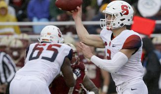 Syracuse quarterback Eric Dungey (2) passes as he gets a block from offensive lineman Jamar McGloster (65) during the first half of an NCAA college football game against Boston College, Saturday, Oct. 22, 2016, in Boston. (AP Photo/Mary Schwalm)