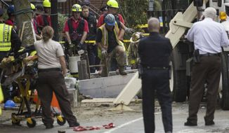 This photo provided by WBUR.ORG shows emergency personnel at the scene of a water main break, Friday, Oct. 21, 2016 in Boston.  Two workers in Boston were killed when a water main gave way and flooded a deep trench where they were working. The Boston Fire Department recovered the bodies Friday night in the South End neighborhood after several hours of painstaking work.  (Jesse Costa/WBUR.ORG via AP)