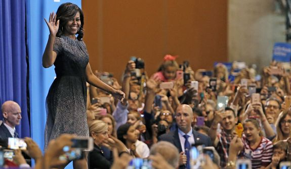 First lady Michelle Obama waves to supporters as she takes the stage at a campaign rally for Hillary Clinton on Oct. 20 in Phoenix. (Associated Press)