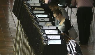 People cast ballots in Miami on Monday on the first day of early voting. (Associated Press)