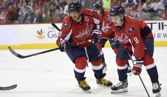 Washington Capitals left wing Alex Ovechkin (8) and defenseman Dmitry Orlov (9), both of Russia, look on during the first period of an NHL hockey game against New York Rangers, Saturday, Oct. 22, 2016, in Washington. (AP Photo/Nick Wass)