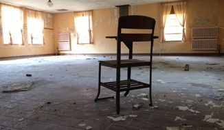 In this Oct. 17, 2016 photo, a classroom desk sits inside an abandoned building at the former Mansfield Training School in Mansfield, Conn. Many buildings at the former mental institution, now part of the University of Connecticut's Depot Campus, remain as they were when the school took over the property in 1993. (AP Photo/Pat Eaton-Robb)