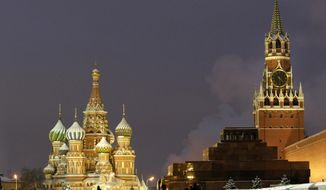 In this Dec. 10, 2009, file photo, people walk in Red Square, with St. Basil Cathedral, left, the Kremlin's Spassky Tower, right back, and Lenin Mausoleum, right, in Moscow, Russia. (AP Photo/Misha Japaridze, File)