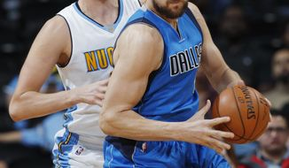 FILE - This Oct. 21, 2016 file photo shows Dallas Mavericks center Andrew Bogut, front, working the ball inside for a shot as Denver Nuggets center Nikola Jokic defends during the second half of an NBA preseason basketball game in Denver. Roughly 22 percent of NBA players were born outside the United States. As the season is set to begin and talk of demonstrations during the national anthem continue, international players have sought counsel from their African-American teammates to try to relate to problems they never experienced growing up in their countries. (AP Photo/David Zalubowski, file)