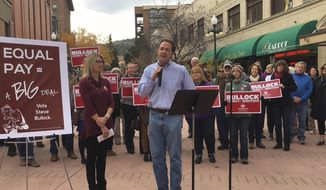 Montana Gov. Steve Bullock, center, addresses a rally for equal pay for women in Helena, Mont., Monday, Oct. 24, 2016. Bozeman businessman Greg Gianforte has now spent more than $5.1 million of his own money to fuel his campaign against Bullock, while the Bullock-backing Democratic Governors Association poured in another $1.5 million into one of the closest governor's races in the nation. (AP Photo/Matt Volz)