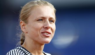 FILE - This is a Wednesday, July 6, 2016 file photo of Russian doping whistleblower Yulia Stepanova who ran under a neutral flag smiles as she arrives in the stadium to compete in a women's 800m heat during the European Athletics Championships in Amsterdam, the Netherlands.  The International Olympic Committee said Monday Oct. 24, 2016 that  it is offering career assistance to the Russian wife and husband team  of Yulia Stepanova and  Vitaly Stepanov who blew the whistle on widespread doping in their homeland.  (AP Photo/Matthias Schrader, File)