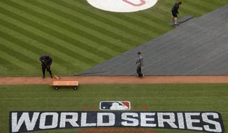 Members of the grounds crew prepare the field for batting practice for baseball's upcoming World Series between the Cleveland Indians and the Chicago Cubs, Monday, Oct. 24, 2016 in Cleveland. (AP Photo/David J. Phillip)