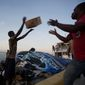 """People unload food and water boated in from the """"Mission of Hope"""" charity after Hurricane Matthew swept through Jeremie, Haiti, on Oct. 8. (Associated Press)"""