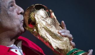 FILE - In this April 22, 2014 file photo, former Brazilian soccer captain Carlos Alberto Torres kisses the World Cup trophy which is part of the FIFA World Cup Trophy Tour, at the Maracana Stadium, in Rio de Janeiro, Brazil. Caros Alberto, a teammate of Pele and the captain of Brazil's World Cup-winning team in 1970, has died. He was 72. (AP Photo/Felipe Dana, File)