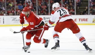 Detroit Red Wings center Frans Nielsen (51) advances the puck as Carolina Hurricanes left wing Viktor Stalberg (25) defends in the second period of an NHL hockey game in Detroit, Tuesday, Oct. 25, 2016. (AP Photo/Paul Sancya)