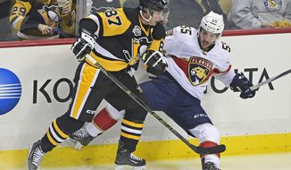Pittsburgh Penguins center Sidney Crosby (87) knocks over Florida Panthers defenseman Jason Demers (55) with a check during the first period of an NHL hockey game on Tuesday, Oct. 25, 2016, in Pittsburgh. (AP Photo/Fred Vuich)