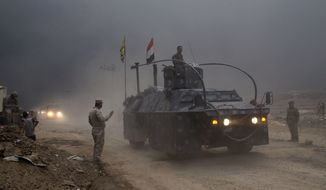 An Iraqi Federal Police vehicle passes through a checkpoint in Qayara, some 50 kilometers south of Mosul, Iraq, Wednesday, Oct. 26, 2016. Islamic State militants have been going door to door in farming communities south of Mosul, ordering people at gunpoint to follow them north into the city and apparently using them as human shields as they retreat from Iraqi forces. Witnesses to the forced evacuation describe scenes of chaos as hundreds of people were driven north across the Ninevah plains and into the heavily-fortified city, where the extremists are believed to be preparing for a climactic showdown.  (AP Photo/Marko Drobnjakovic)