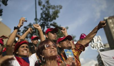 """Supporters of Venezuela's President Nicolas Maduro show their support during a political rally against Congress in Caracas, Venezuela, Tuesday, Oct. 25, 2016. After the government suspended a recall referendum seeking President Nicolas Maduro's removal last week, the opposition-controlled congress began debating his """"constitutional situation."""" Lawmakers vow to present evidence that Maduro is a dual Colombian citizen and therefore constitutionally ineligible to hold Venezuela's highest office. (AP Photo/Alejandro Cegarra)"""