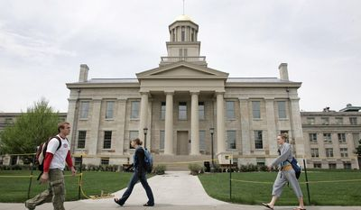 FILE - In this May 3, 2006, file photo, University of Iowa students walk past the Old Capitol building in Iowa City, Iowa a few days before the building was to open to the public for the first time since being heavily damaged in a fire on Nov. 20, 2001. The University of Iowa filed a lawsuit in October 2016 against the contractor it hired to restore and improve the campus icon after the 2001 fire destroyed parts of the building. The university says it discovered construction deficiencies in 2011 that the contractor has since refused to correct. (AP Photo/Charlie Neibergall, File)