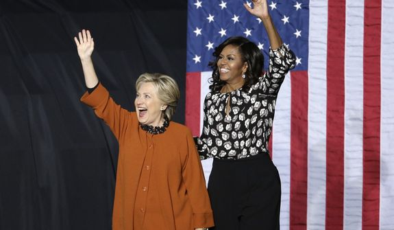 Democratic presidential candidate Hillary Clinton and first lady Michelle Obama wave to supporters during a campaign rally in Winston-Salem, N.C., Thursday, Oct. 27, 2016. (AP Photo/Chuck Burton)