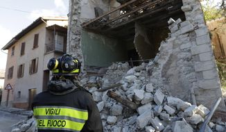 A firefighter looks at a damaged house in the small town of Visso in central Italy, Thursday, Oct 27, 2016, after a 5.9 earthquake destroyed part of the town. A pair of strong aftershocks shook central Italy late Wednesday, crumbling churches and buildings, knocking out power and sending panicked residents into the rain-drenched streets just two months after a powerful earthquake killed nearly 300 people. (AP Photo/Alessandra Tarantino)