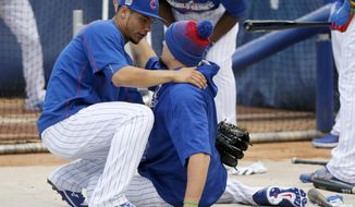 Chicago Cubs' Willson Contreras, left, hugs Kyle Schwarber as Schwarber stretches during batting practice for Friday's Game 3 of the Major League Baseball World Series against the Cleveland Indians, Thursday, Oct. 27, 2016, in Chicago. (AP Photo/Charles Rex Arbogast)