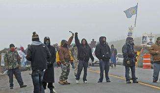 Protesters cover the roadway of Highway 1806 at the site of the New Camp on Pipeline Easement on Wednesday morning, Oct. 26, 2016. The prospect of a police raid on an encampment protesting the Dakota Access pipeline faded as night fell Wednesday, with law enforcement making no immediate move after protesters rejected their request to withdraw from private land. Activists fear the nearly 1,200-mile pipeline could harm cultural sites and drinking water for the Standing Rock Sioux tribe. (Tom Stromme/The Bismarck Tribune via AP)