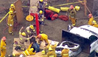 In this still frame from video provided by KTTV Fox11 News, Los Angeles firefighters hoist a delivery truck driver from a deep and narrow hole at a construction site in the Beverly Crest area of Los Angeles, Thursday, Oct. 27, 2016. The 30-year-old man fell up to 50 feet down the 24-inch-diameter hole and landed feet-first on compacted soil, according to Fire Department spokesman Brian Humphrey. Firefighters pumped fresh air into the hole and lowered a radio to the man, who remained conscious and was able to put on a harness attached to a rope. Firefighters used a fire truck's ladder like the boom of a crane to hoist the man up. (KTTV Fox11 News via AP)