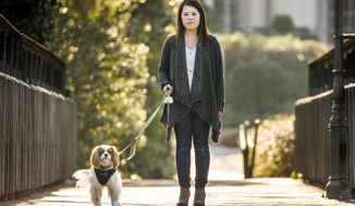 In this Feb. 25, 2015, Ebola survivor Nina Pham walks her dog Bentley in Dallas.   Ebola no longer dominates the headlines, but for an estimated 17,000 survivors of the largest Ebola outbreak in history the struggle is not over. Many who survived the West African outbreak that sickened nearly 30,000 people between 2014 and 2016 are living with a constellation of long-term symptoms known as post-Ebola syndrome.  (Smiley N. Pool/The Dallas Morning News via AP)