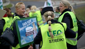 """Flight attendants gather in front of their headquarters during a strike in Cologne, Germany, Thursday, Oct. 27, 2016. German airline Lufthansa has canceled hundreds of flights at its budget unit Eurowings, affecting some 40,000 passengers, because of a strike by cabin crew. Poster reads: """" Fan of phone calls on off-days"""".(Oliver Berg/dpa via AP)"""