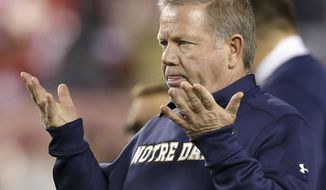 FILE - In this Oct. 31, 2015, file photo, Notre Dame head coach Brian Kelly gestures to his players as they warm up before an NCAA college football game against Temple, in Philadelphia. Miami and Notre Dame can only wish their game Saturday could come close to living up to the intensity the series had nearly three decades ago when for three straight seasons the winner was the national champion. (AP Photo/Mel Evans, File)