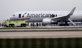 Firefighters extinguish flames from American Airlines Flight 383, flight bound for Miami, which caught fire on the runway at O'Hare International Airport, Friday, Oct. 28,  2016, as it was taking off. (Antonio Perez/Chicago Tribune via AP)