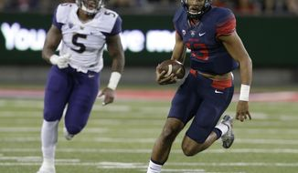 FILE  - In this Sept. 24, 2016, file photo, Arizona quarterback Brandon Dawkins (13) runs away from Washington linebacker Joe Mathis during the first half of an NCAA college football game in Tucson, Ariz. Stanford and Arizona were once teams with designs on winning their respective divisions. Heaidng into Saturday's game, their lone goal now is to become bowl eligible.  (AP Photo/Rick Scuteri, File)