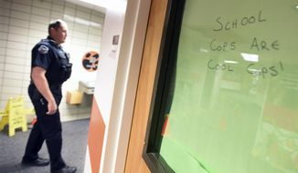 "ADVANCE FOR WEEKEND EDITIONS OCT. 29-30 - In this Oct. 19, 2016 photo, A small sign reads ""school cops are cool cops"" as Greeley Police Officer Brad Luebke walks through the hallway of Brentwood, 2600 24th Ave Ct., in Greeley, Colo.(Joshua Polson/The Greeley Tribune via AP)"