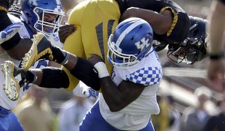 Missouri quarterback Marvin Zanders, top, is stopped by Kentucky safety Marcus McWilson after running for a short gain as Kentucky's Kash Daniel, left, gets in on the play during the first half of an NCAA college football game Saturday, Oct. 29, 2016, in Columbia, Mo. (AP Photo/Jeff Roberson)