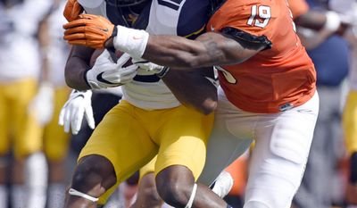 West Virginia wide receiver Gary Jennings (12) struggles to free himself from a tackle by Oklahoma State linebacker Justin Phillips (19) during the first half of an NCAA college football game in Stillwater, Okla., Saturday, Oct. 29, 2016.(AP Photo/Brody Schmidt)