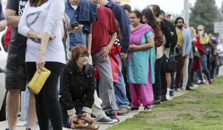 """FILE - In this Oct. 30, 2016 file photo, a woman kneels to take a """"back break"""" while waiting in line at a weekend early voting polling place at the North Hollywood branch library in Los Angeles. The FBI's disclosure that it was reviewing emails related to Hillary Clinton's email investigation will make no difference to tens of millions of voters who have already cast ballots.  (AP Photo/Reed Saxon, File)"""