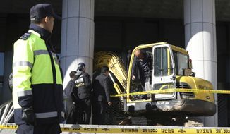 Police officers examine an excavator after a man rammed into a gate near a Seoul prosecutors' office in Seoul, South Korea, Tuesday, Nov. 1, 2016. Police detained  the man. The man later told investigators he tried to meet and help the woman with her death because she told reporters she deserves death. (Kim Do-hoon/Yonhap via AP)