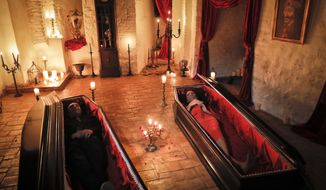 Tami Varma, right, and her brother Robin, the grandchildren of Devendra Varma, a scholar of English gothic tales and an expert in vampire lore, pose in coffins, at the Bran Castle, in Bran, Romania, Monday, Oct. 31, 2016. A Canadian brother and sister are passing Halloween night curled up in red velvet coffins in the Transylvanian castle that inspired the Dracula legend, the first time in 70 years anyone has spent the night in the gothic fortress, after they bested 88,000 people who entered a competition hosted by Airbnb to get the chance to dine and sleep at the castle in Romania. A portrait of medieval prince Vlad the Impaler is placed on the wall. (AP Photo/Vadim Ghirda)