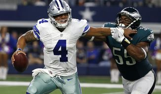 Dallas Cowboys quarterback Dak Prescott (4) fights off pressure from Philadelphia Eagles defensive end Brandon Graham (55) before throwing a pass in the first half of an NFL football game, Sunday, Oct. 30, 2016, in Arlington, Texas. (AP Photo/Michael Ainsworth)