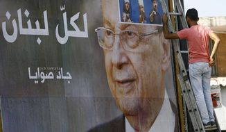 "A worker hangs a billboard showing Christian leader Michel Aoun with Arabic that reads ""For all Lebanon,"" in the southern port city of Sidon, Lebanon, Sunday, Oct. 30, 2016. Aoun, an 81-year-old veteran Christian politician, is set to be elected by Parliament on Monday as part of a political deal that's expected to be another boost for President Bashar Assad in neighboring Syria. (AP Photo/Mohammed Zaatari)"