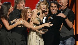 "FILE - This Nov. 11, 2009 file photo shows Taylor Swift and her band reacting as she won""Entertainer of the Year"" award at the 43rd Annual Country Music Awards in Nashville, Tenn.  Swift became the youngest person to win the top prize, entertainer of the year. (AP Photo/Josh Anderson, File)"