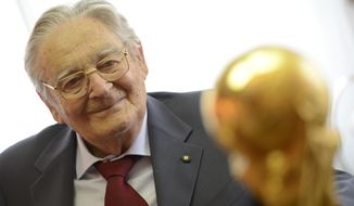 In this photo taken on Thursday, June 3, 2014, Italian goldsmith and sculptor Silvio Gazzaniga poses with his most important work, the FIFA World Cup at GDE Bertoni factory in Paderno Dugnano, near Milan, Italy. Silvio Gazzaniga, the sculptor who created the World Cup trophy, has died. He was 95. Gazzaniga designed and created the World Cup trophy in 1971 after Brazil retained the right to keep the Jules Rimet trophy by winning its third World Cup in 1970. (AP Photo/Giuseppe Aresu)