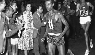 FILE - In this Sept. 10, 1960 file photo, Ethiopia's Abebe Bikila (11) runs barefoot as he leads in the final stages of the Olympic Marathon in Rome, Italy, followed closely by Morocco's Abdesian Rhadi, right. A federal judge ruled Monday, Oct. 31, 2016, that Vibram, the maker of a popular line of minimalist running shoes, does not have to pay damages for naming some of its models after Bikila. (AP Photo/File)