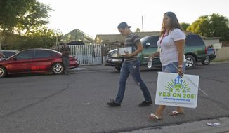 In this photo taken Oct. 18, 2016, workers with the Living United for Change in Arizona organization, known as LUCHA, canvas a south Phoenix neighborhood knocking on the doors of registered voters to advocate for the passage of Proposition 206, which would increase the state's minimum wage. The organization was part of a non-partisan voter registration drive this year in Latino neighborhoods that resulted in 150,000 new registered voters. Democrats hope Latinos in Arizona will help turn the traditionally conservative state blue for the first time in 20 years. (AP Photo/Astrid Galvan)
