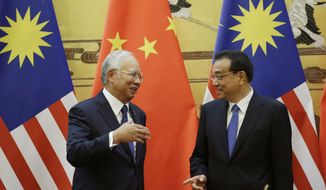 Malaysia's Prime Minister Najib Razak, left, and China's Premier Li Keqiang chat during a signing ceremony following their meeting at the Great Hall of the People in Beijing Tuesday, Nov. 1, 2016. (Jason Lee/Pool Photo via AP)
