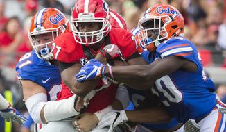 FILE - In this Saturday, Oct. 29, 2016, file photo, Florida defensive back Marcus Maye (20) and defensive lineman Joey Ivie (91) tackle Georgia running back Nick Chubb (27) during the first half of an NCAA football game in Jacksonville, Fla.  Even with talented running backs Nick Chubb and Sony Michel, Georgia is still looking for answers on offense after being held to a season-low 164 yards in last week's 24-10 loss to Florida. The Bulldogs are preparing to play at Kentucky on Saturday. (AP Photo/Stephen B. Morton, File)