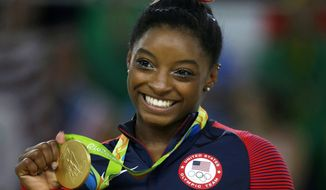 FILE - In this Aug. 16, 2016 file photo, United States gymnast Simone Biles displays her gold medal for floor during the artistic gymnastics women's apparatus final at the 2016 Summer Olympics in Rio de Janeiro, Brazil. Biles was named one of Glamour's Women of the Year, Tuesday, Nov. 1, and will be honored at a ceremony in Los Angeles on Nov. 14. (AP Photo/Rebecca Blackwell, File)