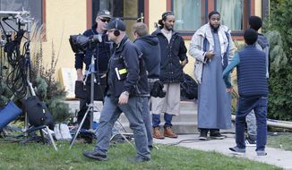 """In this Oct. 12, 2016 photo, Somali actors and film crew wait outside a home in Minneapolis for their role in filming of the proposed HBO series """"Mogadishu, Minnesota."""" Somali-Canadian rapper, K'naan, who is directing and writing the proposed series, wants to tell a story of an immigrant coming to America and trying to adjust. (AP Photo/Jim Mone)"""