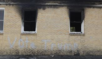 """""""Vote Trump"""" is spray painted on the side of the fire damaged Hopewell M.B. Baptist Church in Greenville, Miss., Wednesday, Nov. 2, 2016.  Fire Chief Ruben Brown tells The Associated Press that firefighters found flames and smoke pouring from the sanctuary of the church just after 9 p.m. Tuesday. (AP Photo/Rogelio V. Solis)"""