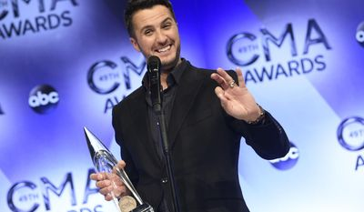 FILE - In this Nov. 4, 2015 file photo, Luke Bryan, winner of the award for entertainer of the year, poses in the press room at the 49th annual CMA Awards in Nashville, Tenn.  Bryan is again nominated for entertainer of the year at the Country Music Association Awards on Wednesday, Nov. 2, an award he won the last two consecutive years. (Photo by Evan Agostini/Invision/AP, File)