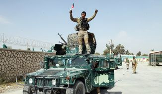 In this Oct. 2, 2015, file photo, an Afghan soldier raises his hands as a victory sign, in Kunduz city, north of Kabul, Afghanistan. (AP Photo/Dehsabzi, File)