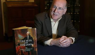 """Steven Bullock, professor of humanities at Worcester Polytechnic University, poses with his new book, """"Tea Sets and Tyranny: The Politics of Politeness in Early America,"""" Wednesday, Nov. 2, 2016, in Worcester, Mass. Political bombast is nothing new: America's founding fathers weren't above pounding tables and accusing each other of disloyalty or treason. (AP Photo/Elise Amendola)"""