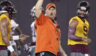 FILE- In this Thursday, Aug. 4, 2016, file photo, Virginia Tech head coach Justin Fuente directs offensive drills as quarterbacks Jerod Evans (4) left, and Brenden Motley (9) right, listen during NCAA college football practice in Blacksburg, Va. One of the things that has most impressed first-year Virginia Tech coach Justin Fuente is how many fans of the No. 23 Hokies show up everywhere they play.  (Matt Gentry/The Roanoke Times via AP, File)